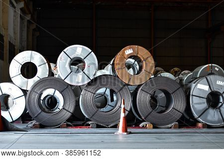 Stack of steel coil in storage warehouse. Steel coils handling equipment. Steel warehouse and logist