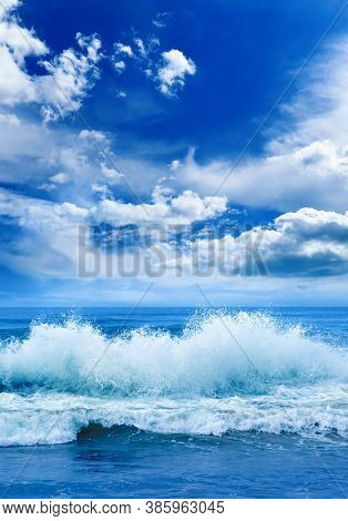 Bright ocean vertical landscape in blue tones. Sea waves and beautiful sky with white clouds.