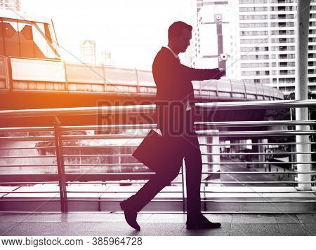 Businessman Walking On The Skywalk Hastily. In His Hand Is A Black Leather Briefcase. With Flare Lig