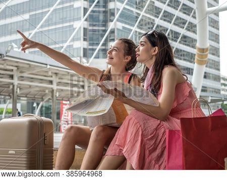Two Beautiful Women Using Map As To Travel Abroad During The Holiday Season.