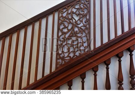 Wooden Brown Railing Of The Stairs Against The Background Of A White Wall. At The Bottom Of The Balu