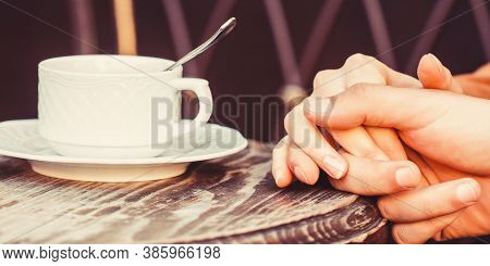 Female And Man Hands Holding Cup Of Coffee. Couple In Love Holding Hands With Coffee. Couple Holding