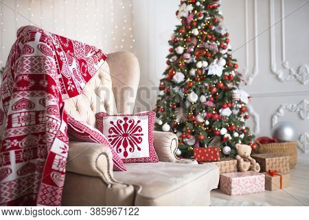 Christmas Tree With Red And White Decor In A White Living Room With Gifts In Boxes, A Chair With Pil
