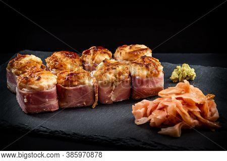 Served Warm Sushi Rolled In Bacon With Ginger And Wasabi On A Black Stone Plate.