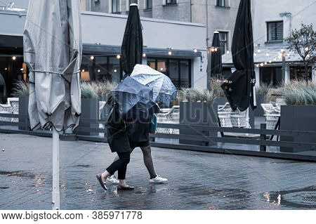 Girls Take Shelter With Umbrellas From Light Rain And Strong Wind Outside In Bad Weather.