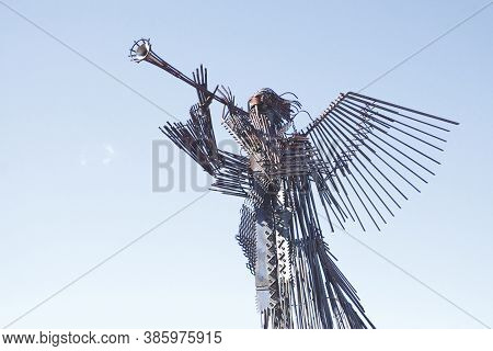 Chernobyl, Ukraine, March 14, 2020. Metal Sculpture Of A Trumpeting Angel Against The Blue Sky In Ch