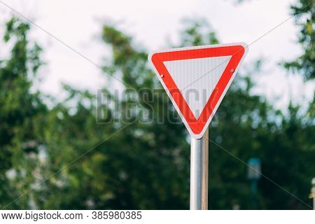 Sign Give Way On A Blurred Street And White Sky. Red And White Road Sign In The Form Of A Triangle W