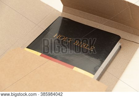 Mail Shipping Box With Holy Bible Being Opened. Top View. Close-up.