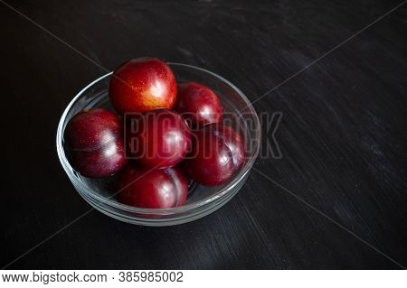 Red Mellow Plums In Transparent Glass Bowl On Dark Background. Close-up.