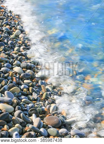Oval Pebbles And Wave On The Beach Closeup, Background