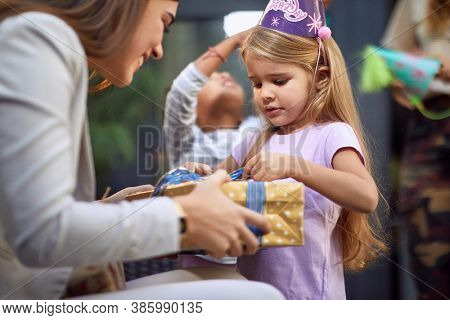 little caucasian girl unwrapping birthday present from young adult female brunette