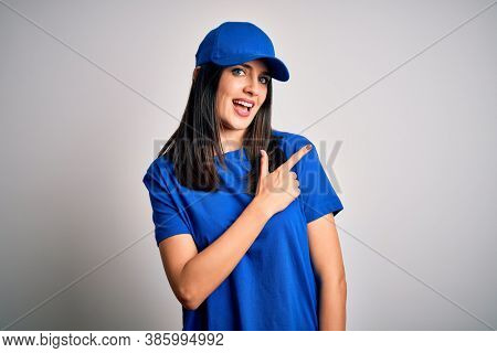 Young delivery woman with blue eyes wearing cap standing over blue background cheerful with a smile of face pointing with hand and finger up to the side with happy and natural expression on face