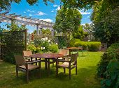 a wooden dining table set in lush garden setting poster