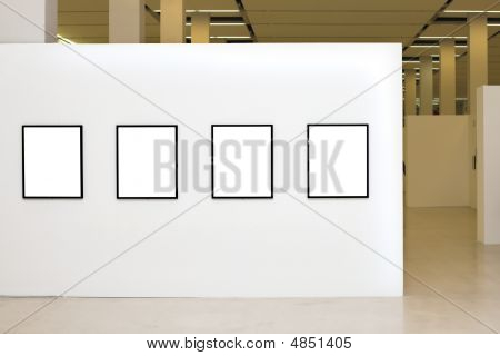 Exhibition With Four Empty Frames On White Walls