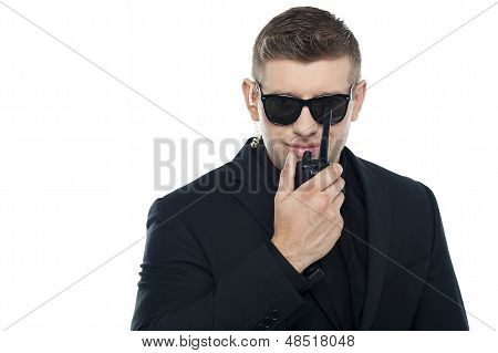 Smart Young Security Personnel Communicating Over The Walkie-talkie