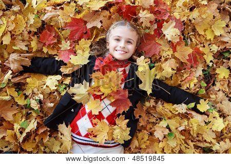 Autumn fun - lovely girl has a fun in autumn leaves, happy child