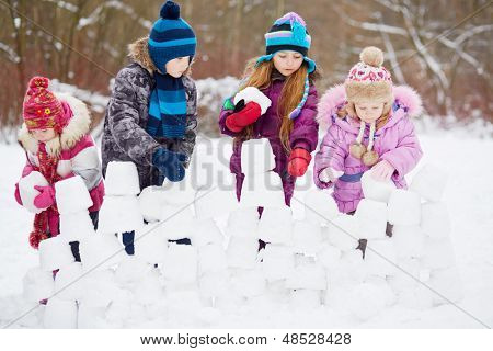 Children work at building wall from snow blocks in winter park