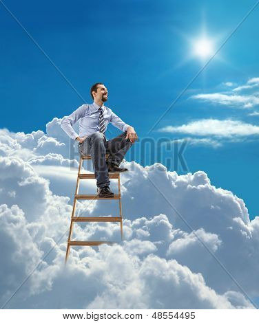 young confident businessman sits atop at the ladder high in the sky