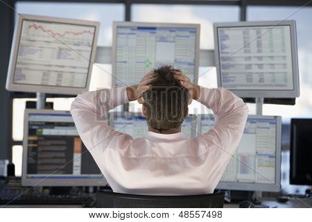 Rear view of stock trader with hands on head looking at multiple computer screens