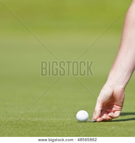 SAINT-OMER, FRANCE. 17-06-2010, A golfer marks his position on a green during the European Tour, 14th Open de Saint-Omer, part of the Race to Dubai tournament and played at the AA Saint-Omer Golf Club