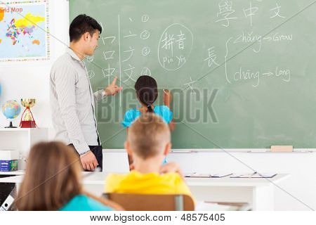 elementary school student writing answer on the board with teacher standing next to her