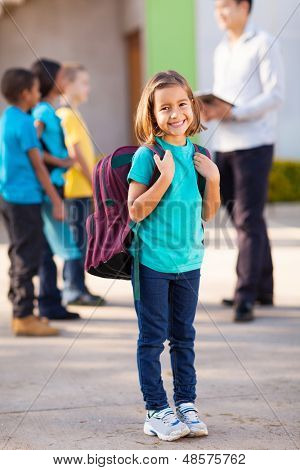 happy primary school student carrying backpack with classmates and teacher on background