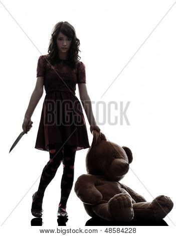 one caucasian strange young woman killer holding  bloody knife an teddy bear in silhouette white background