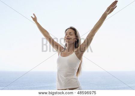 Young woman with arms outstretched and eyes closed standing against ocean