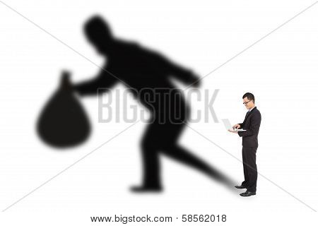 Businessman Using Laptop With Thief Shadow