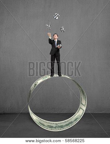 Businessman Throwing And Catching Money Symbols On Money Circle