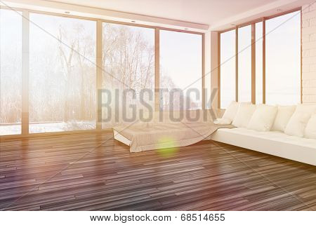 Bright airy sparsely furnished living room with a corner couch and throw rug on a wooden parquet floor surrounded by floor-to-ceiling glass windows letting in bright sunlight with lens flare