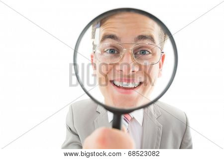 Geeky businessman looking through magnifying glass on white background