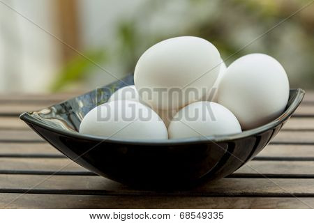 Bowl full of eggs isoated on wooden table