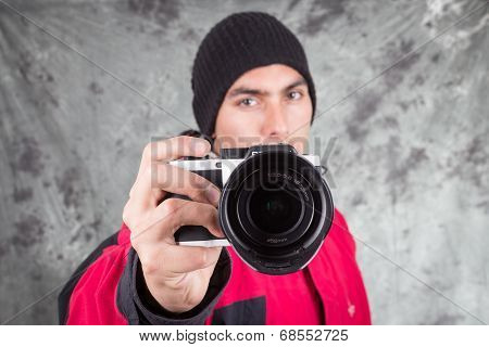 closeup of young handsome man wearing red jacket and black beanie over grey background