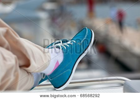 A Pair Of Human Legs In Pants And Bright Blue Topsiders