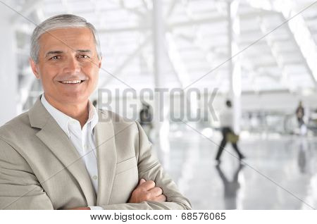 Closeup of a mature businessman with his arms folded in an airport concourse. The man is smiling at the camera with blurred passengers in the background.