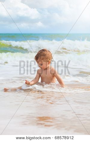 Little Girl Playing With Sand At The Sea