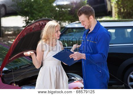 Mechanic Showing Clipboard To Angry Woman By Breakdown Car
