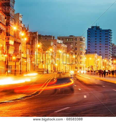 Colorful sunset in Old Havana with  the street lights of El Malecon and light trails from the passing cars