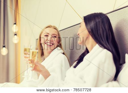 hotel, travel, friendship and happiness concept - smiling girlfriends with champagne glasses in bed