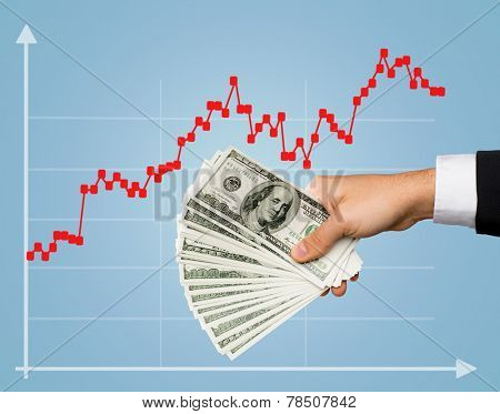 business, finances, people, investments and wealth concept - close up of male stockbroker hand holding dollar cash money over blue background and forex growth chart