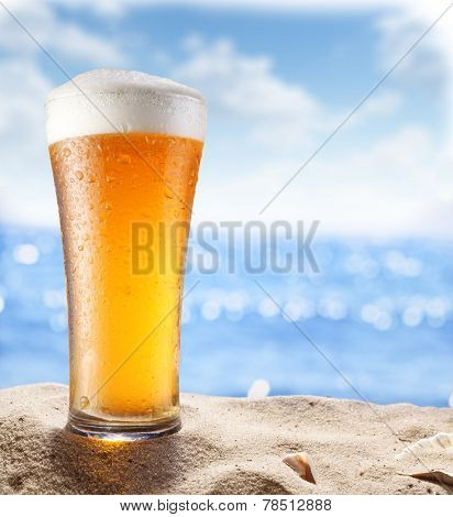 Ice beer glass in the sand. Blurred sea at the background.