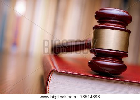 Judges wooden gavel resting on a large red law book on a table in court in a conceptual image of justice and law enforcement poster
