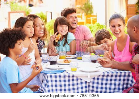 Two Families Eating Meal At Outdoor Restaurant Together