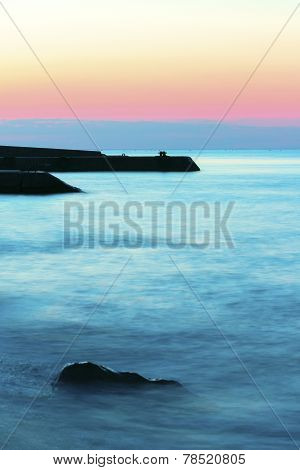 Sunrise on beach with rocks and sea