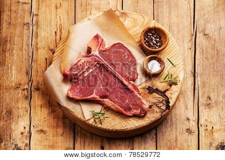 Raw Fresh Meat T-bone Steak With Salt And Pepper On Cutting Board On Wooden Background