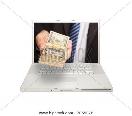 Businessman Handing Stack Of Money Through Laptop Screen