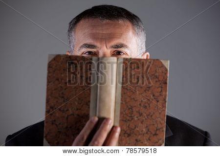 Mature Man Behind An Ancient Book