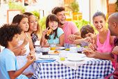 Two Families Eating Meal At Outdoor Restaurant Together poster