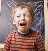 little cute boy screaming and crying at school near blackboard poster